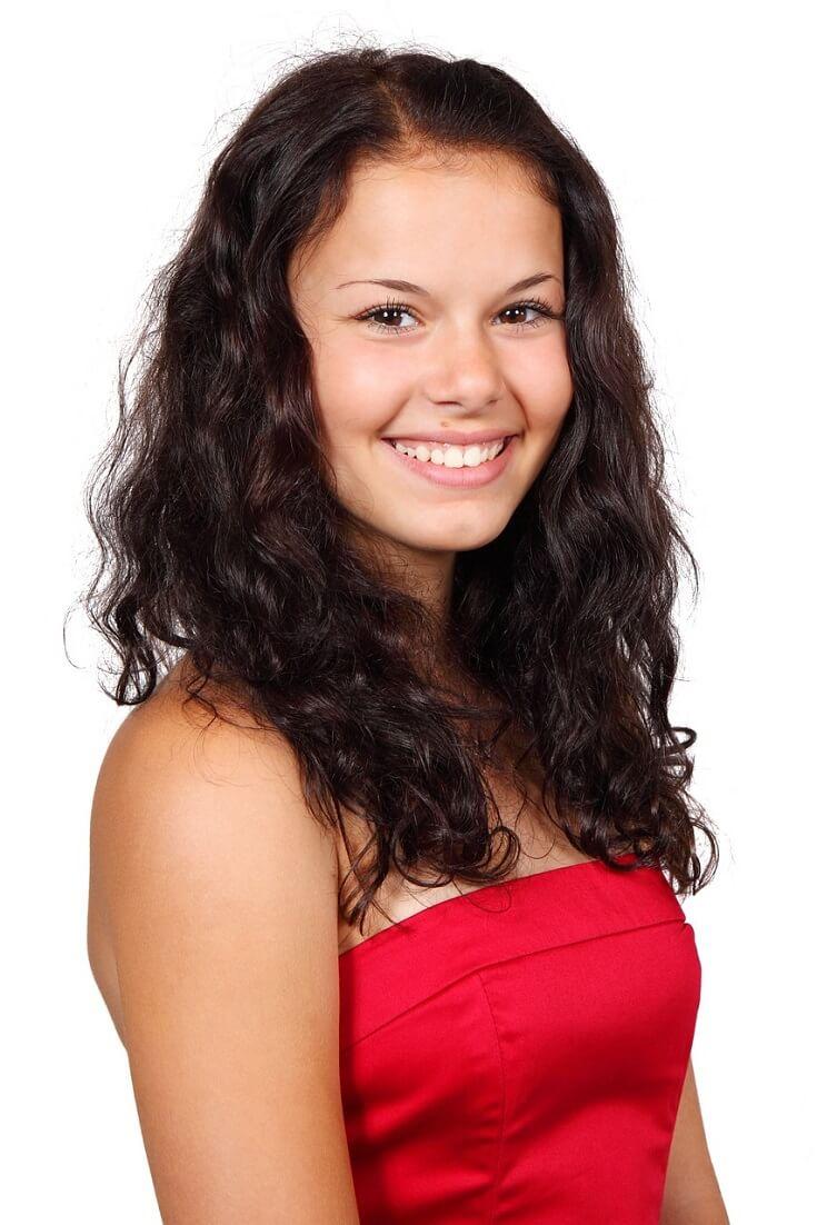 красивая улыбающаяся девушка с вьющимися волнистыми волосами